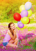 Pretty girl holding colorful balloons — Stock Photo