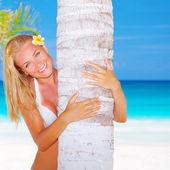 Sexy woman hug palm tree — Stock Photo