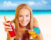 Woman with cocktail and sunblock on the beach — Stock Photo