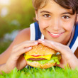Happy boy eating burger — Stock Photo