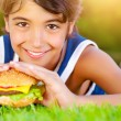 Pretty boy eat burger outdoors — Stock Photo #26484485