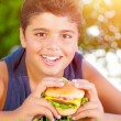 Arabic boy eating burger outdoors — Stock Photo #26484487