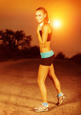 Woman doing exercise at sunset — Stock Photo