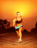 Sporty woman running on sunset — Stock Photo