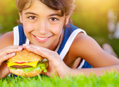 Pretty boy eat burger outdoors — Stock Photo
