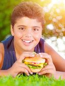 Arabic boy eating burger outdoors — Stock Photo