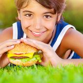Roztomilý chlapec jíst hamburger — Stock fotografie