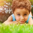Baby boy lying down on green field — Stock Photo