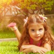 Little girl lying down on green grass — Stock Photo