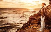 Tourist girl on sunset on the cliff — Stock Photo