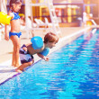 Stock Photo: Little boy jumping into the pool