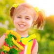 Stock Photo: Happy little girl with sunflowers