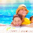 Happy family in the pool — Stock Photo #27720747