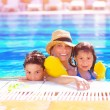 Stock Photo: Mother with kids in poolside
