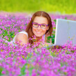 Pretty woman with laptop on floral field — Stock Photo