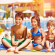 Stock Photo: Three kids eating near pool