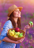 Happy woman with basket of apples — Stock Photo