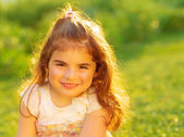 Cute little girl on green field — Stock Photo