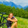 Cheerful female with bicycle on green field — Stock Photo