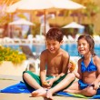 Stock Photo: Happy kids eating near pool
