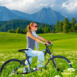 Active woman on bicycle in mountains — Stock Photo