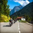 Group of bikers on the road in Alps — Stock Photo