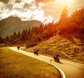 Bikers on mountains road in sunset — Stock Photo