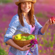 Happy girl with basket of apples — Stock Photo