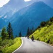 Moto racers on mountainous road — Stok fotoğraf