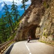 Biker riding into mountainous tunnel — Stock Photo