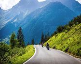 Moto racers on mountainous road — Stock Photo
