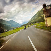 Biker race across mountainous village — Stock Photo