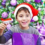 Boy enjoying Christmas gift — Stock Photo #32244601