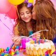 Mother kiss daughter on birthday party — Stock Photo