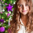 Sweet girl portrait near Christmas tree — Stock Photo