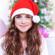 Sweet Santa girl near Christmas tree — Stock Photo