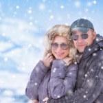 Happy couple under snowfall — Stock Photo