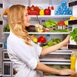 Stock Photo: Happy female search something in fridge
