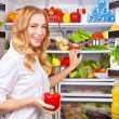 Housewife take red pepper from fridge — Stock Photo