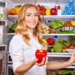 Housewife at the kitchen take red pepper from fridge — Stock Photo