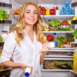 Woman chosen yogurt in opened refrigerator — Stock Photo