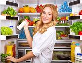 Woman chosen milk in opened refrigerator — Stock Photo