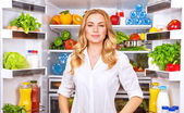 Healthy woman near open fridge — Stock Photo