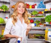 Woman chosen yogurt in opened refrigerator — Stock Photo