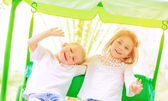 Happy kids on the swing — Stock Photo