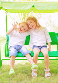 Brother and sister on the swing — Stock Photo