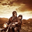 Happy motorcyclists in sunset — Stock Photo