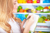 Cute housewife writing list to supermarket — Stock Photo