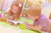 Happy baby boy & girl enjoying homework — Foto Stock
