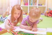 Happy baby boy & girl enjoying homework — Stock Photo